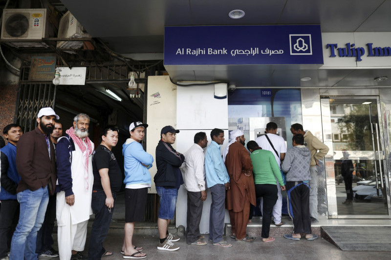 عمال أجانب يصطفون أمام صراف آلي لمصرف الراجحي في العاصمة السعودية الرياض. يشكِّل الوافدون نحو ثلث سكان المملكة البالغ عددهم 34 مليون نسمة