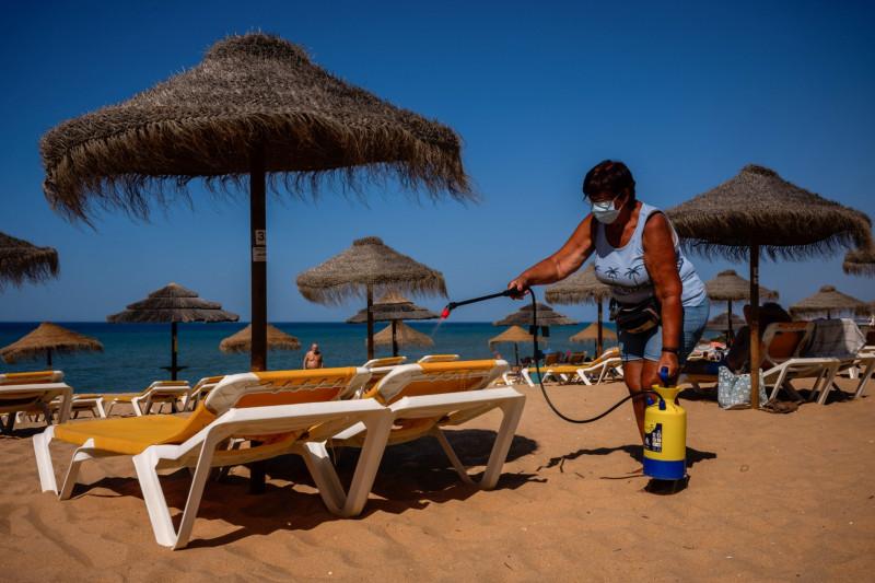 عامل يقوم بتطهير كراسي التشمس على شاطئ كوارتيرا في منطقة الغارف بالبرتغال