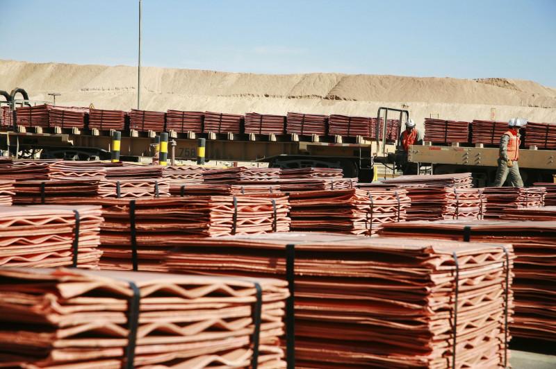 عمال يتفقدون ألواح النحاس المُحملة في عربات السكك الحديدية قرب منجم للنحاس في تشيلي