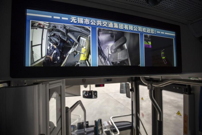شاشة تظهر السائق وهو يسيطر على سيارته دون استخدام دواسات القدم في الحافلة، حيث تدير هواوي مشروعاً تجريبياً لشبكات طرق المركبات المستقلة في ووكسي، بالصين في 22 ديسمبر 2020.