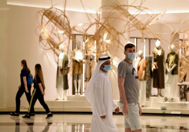 أشخاص يرتدون أقنعة في مول دبي