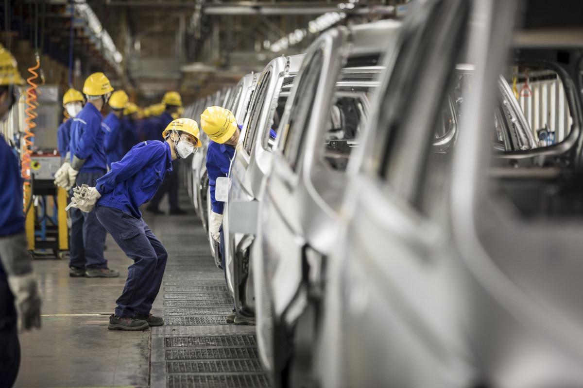 موظفون يتفحصون خط إنتاج سيارات في مصنع تابع لشركتي جنرال موتورز وسايك في إقليم غوانتشي الصيني